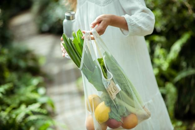 Vegan. femme en robe blanche portant un sac avec des légumes