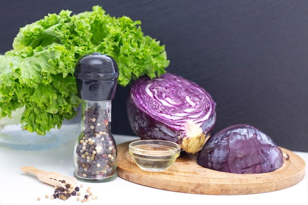 Végétarisme. ingrédients pour une salade légère. chou violet, laitue, pois et huile d'olive sur un tableau blanc.