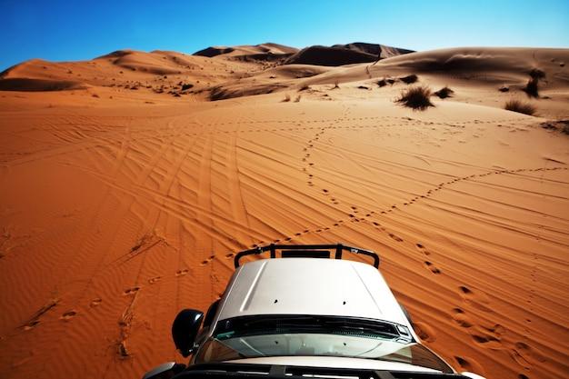 Véhicule 4x4 roulant hors route dans le désert du sahara, le maroc, l'afrique