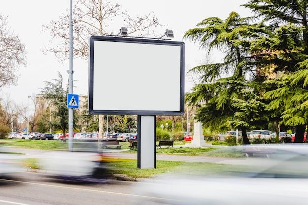 Véhicule flou en passant par le panneau d'affichage vide sur la route
