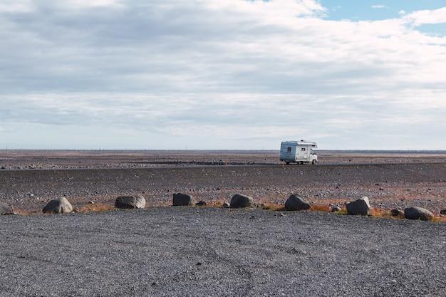 Véhicule de loisirs blanc sur une route vide en islande