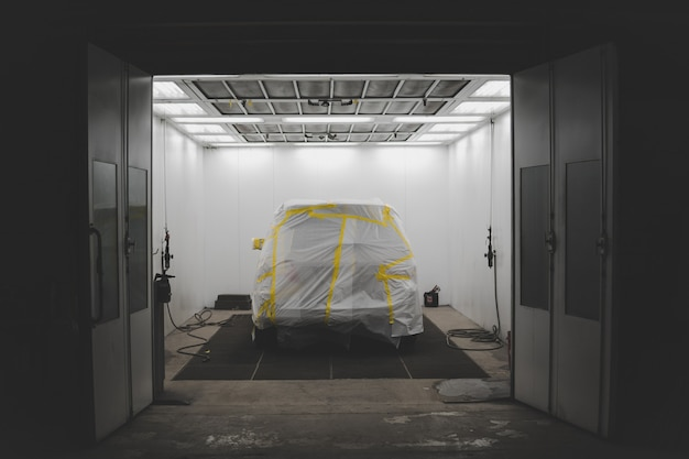 Véhicule recouvert d'une feuille blanche et de ruban jaune dans un garage de service automobile