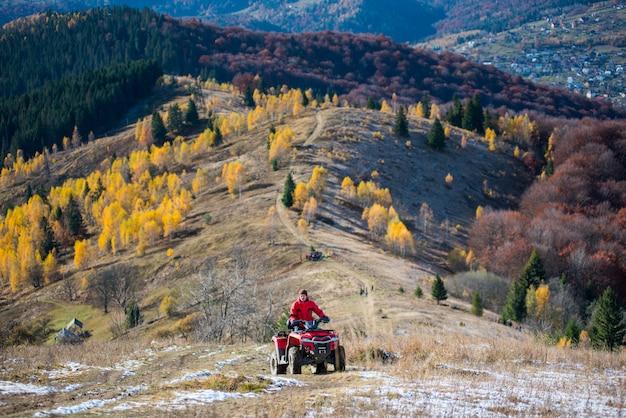 Un véhicule tout-terrain avec un gars sur une route de montagne passe au sommet de la montagne