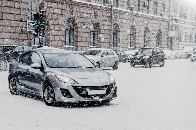 Véhicules couverts de neige pendant le blizzard d'hiver. extrême chute de neige dans une ville européenne
