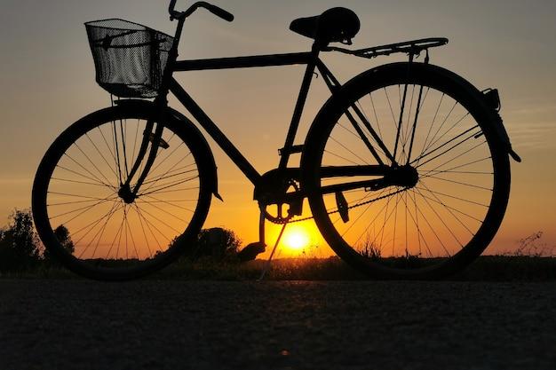 Vélo au coucher du soleil. contour d'une roue de bicyclette au soleil. mise au point sélective