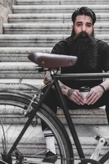 Vélo devant un homme assis sur un escalier tenant une tasse à café