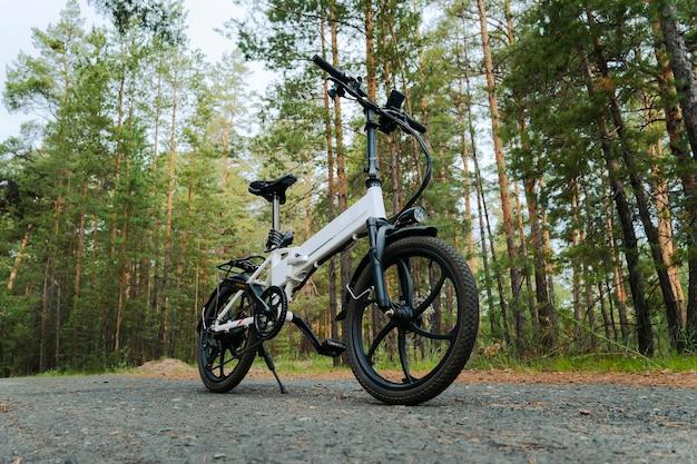Un vélo électrique de couleur blanche sur le fond d'une forêt verte.