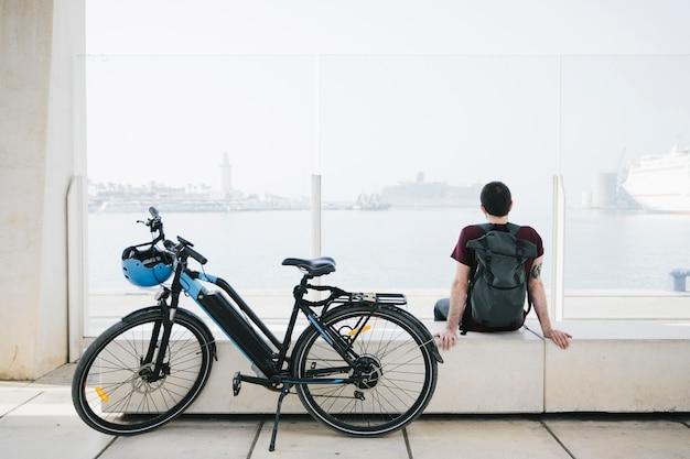 Vélo électrique latéral avec cycliste assis à l'arrière-plan
