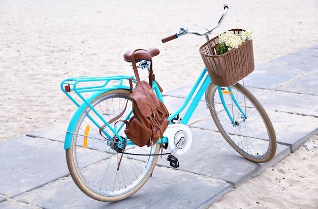 Vélo élégant avec panier de fleurs à l'extérieur