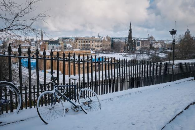 Un vélo enneigé appuyé contre une clôture dans le contexte du centre d'hiver d'édimbourg