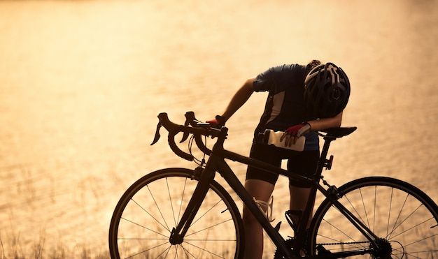 Vélo d'exercice femme elle se sentait fatiguée et boisson relaxante à la rivière