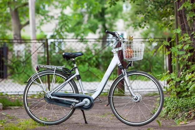 Vélo femme ville blanche avec un ananas dans le panier en journée ensoleillée