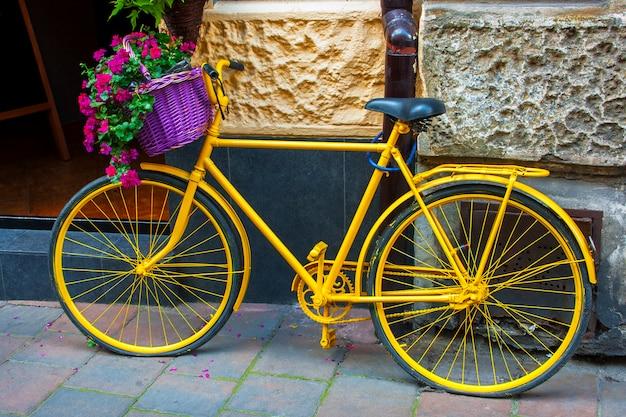 Vélo jaune avec panier de fleurs