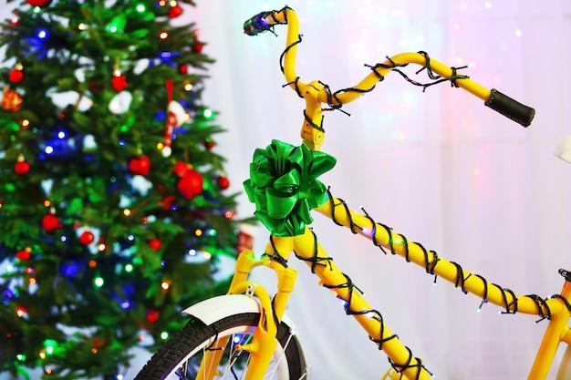 Vélo jaune près de l'arbre de noël