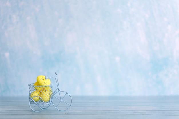 Vélo jouet blanc avec des oeufs de pâques jaunes