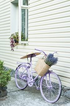 Vélo lilas avec un panier de lavande dans la cour