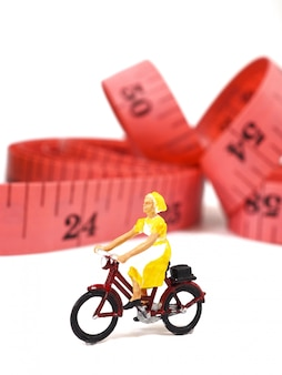 Vélo miniature femme près de pomme verte et ruban à mesurer.
