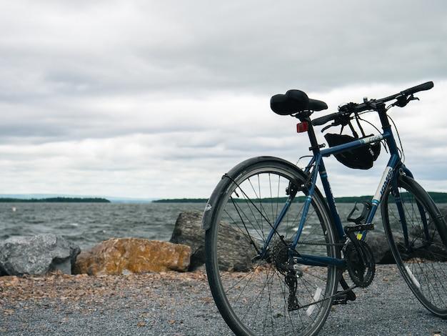 Vélo de montagne bleu garé sur un bord de mer sous un ciel nuageux