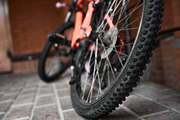 Vélo orange garé par un mur de briques rouges.