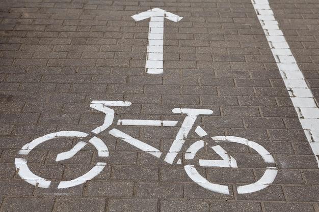 Vélo panneau routier sur piste cyclable peinte sur le trottoir.