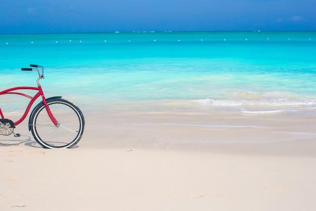 Vélo sur une plage tropicale face à l'océan turquoise et le ciel bleu