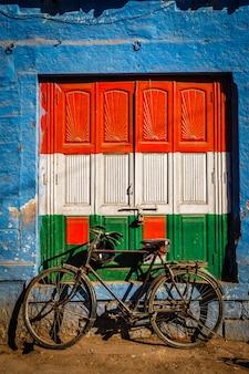 Vélo et porte peints aux couleurs du drapeau national de l'inde. jodhpur, inde