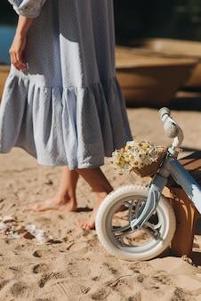 Vélo pour enfants avec un panier et une femme dans une robe bleue sur le sable de l'été