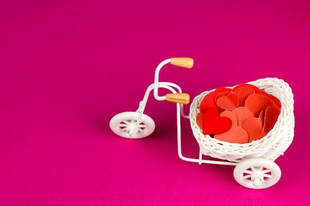 Vélo rétro bijou mignon avec panier en osier blanc plein de coeurs de papier rouge