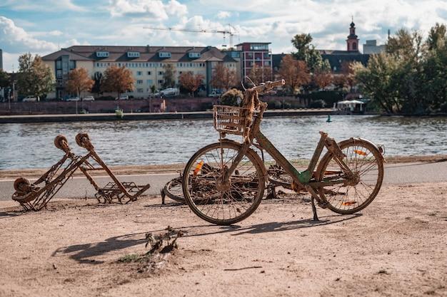 Vélo rouillé et caddie sorti de la rivière dans le parc de la ville.