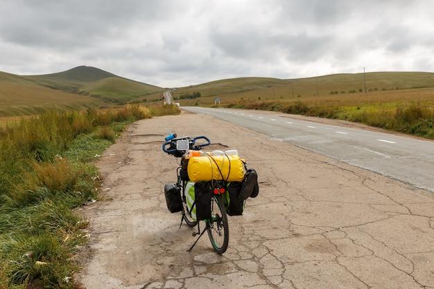 Le vélo de tourisme se tient près de la route goudronnée en mongolie