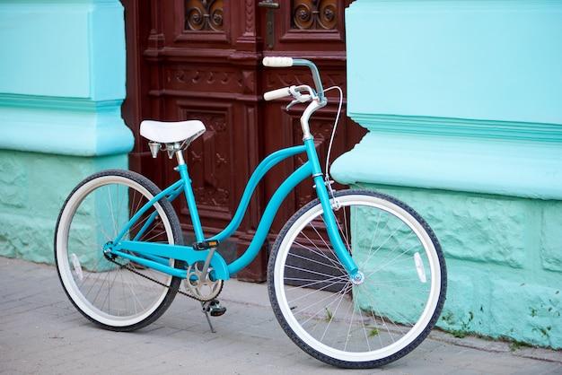 Vélo turquoise vintage avec des éléments blancs garé près de l'ancien bâtiment avec des murs turquiose et des portes anciennes en bois brun.