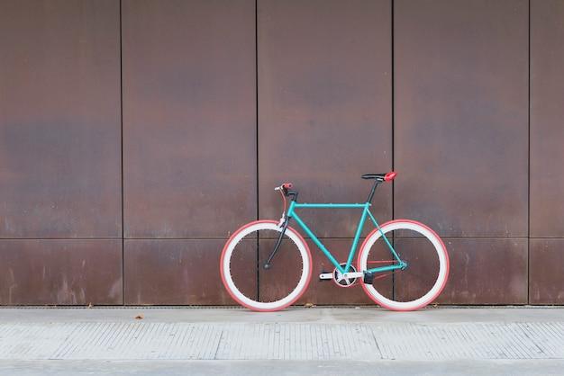 Un vélo de ville engrenage fixe sur un mur marron