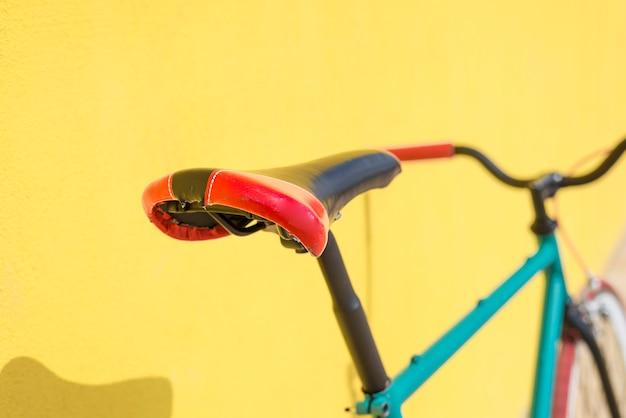 Un vélo de ville fixe engrenage sur un mur jaune