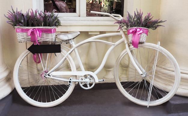 Vélo vintage blanc avec des paniers avec des fleurs de lavande au fond du mur