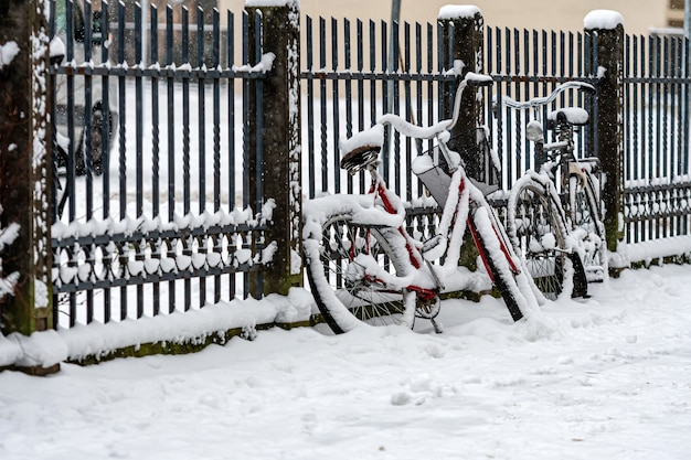 Les vélos couverts de neige sont garés et verrouillés à une clôture sur le trottoir en ville hivernale