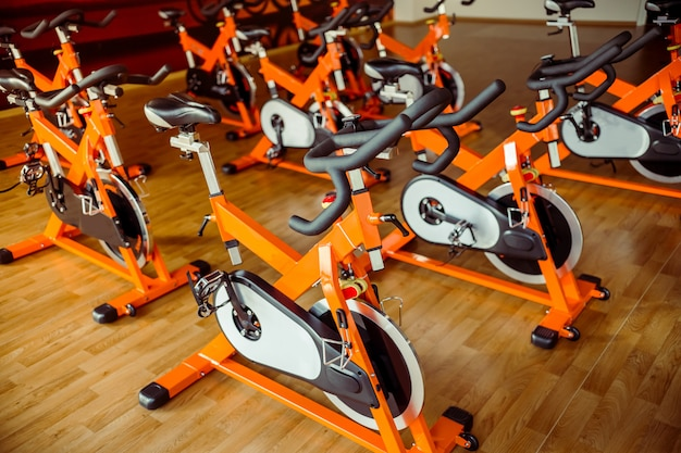 Les vélos dans la salle de sport moderne attendent les gens.