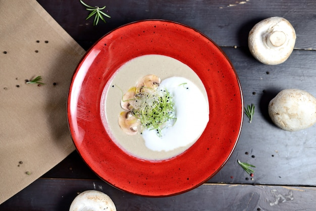 Velouté aux champignons dans une assiette rouge sur une table en bois