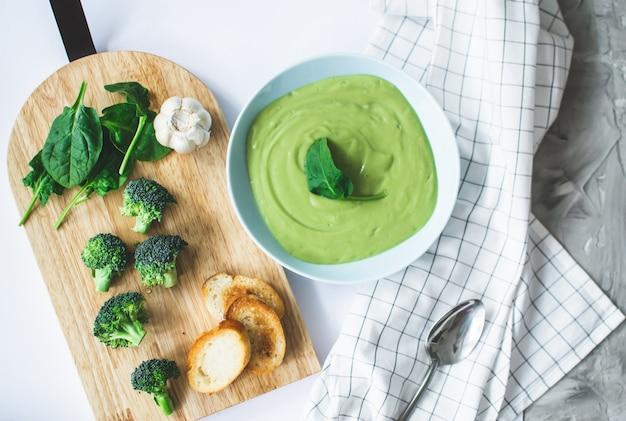 Velouté de brocoli dans une assiette bleue pastel sur fond blanc. la nourriture saine