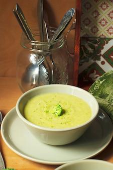 Velouté de brocoli frais sur deux bol en céramique gris sur assiette avec une cuillère sur fond de marbre.