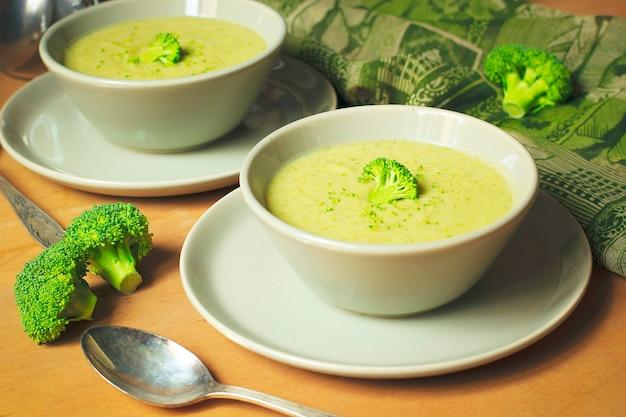 Velouté de brocoli frais sur deux bol en céramique gris sur assiette avec une cuillère sur marbre