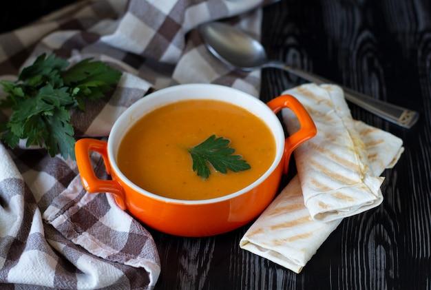 Velouté de carottes citrouille dans une assiette orange avec du fromage pita sur une nappe à carreaux avec fond en bois