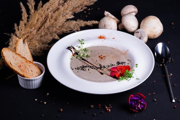 Velouté de champignons avec croûtons sur une surface sombre.