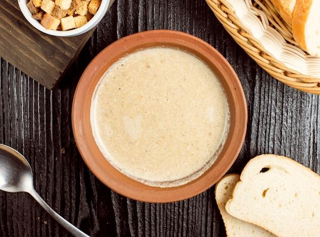 Velouté de champignons dans un bol en poterie avec des craquelins au pain.