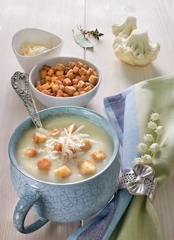 Velouté de chou-fleur dans une tasse bleue avec des croûtons et du parmesan