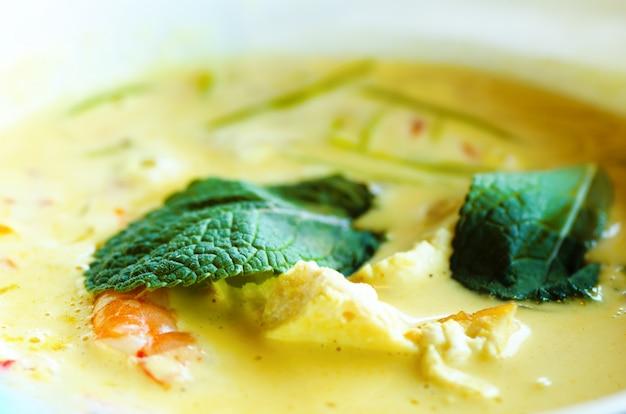 Velouté de lait de coco épicé au curry avec poulet, crevettes tigrées, nouilles soya longues, pousses de soja, citron vert