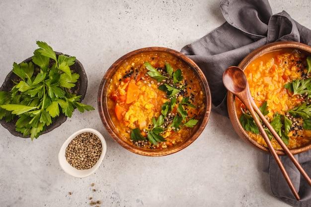 Velouté de lentilles végétalien indien jaune au curry avec persil et sésame dans un bol en bois.