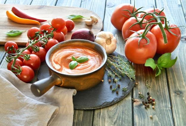 Velouté de tomates dans un bol en céramique sombre avec crème et basilic.
