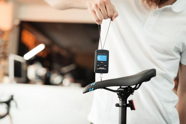 Vendeur au magasin de vélos pèse l'un des vélos.