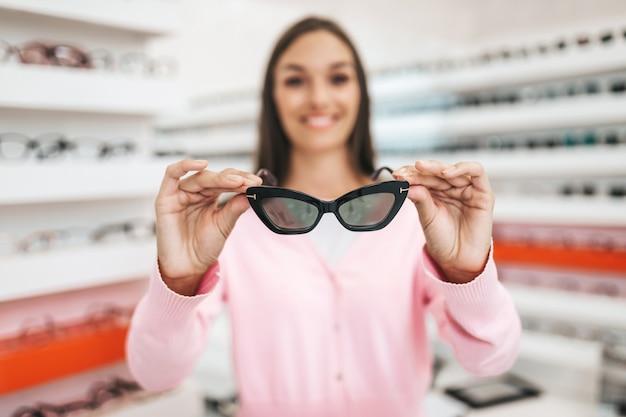 Vendeur et client de femmes d'âge moyen choisissant de nouvelles lunettes dans un magasin d'optique moderne. notion de magasinage.