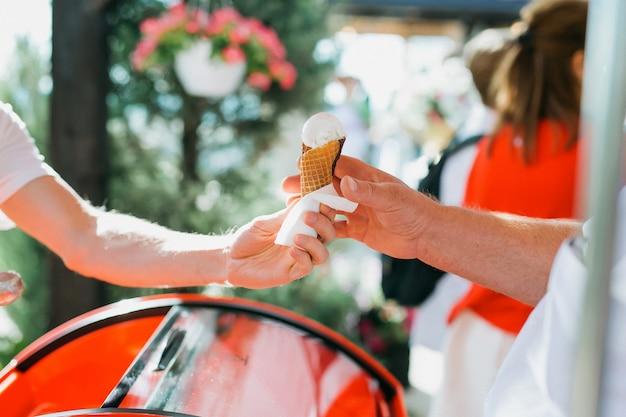 Vendeur de crème glacée donnant un cône de glace au client